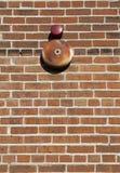 Texturerad bakgrund och varningsklocka för tegelstenvägg Arkivbilder