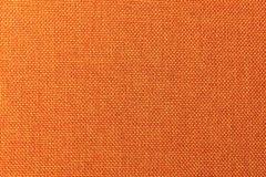 Texturerad bakgrundsyttersida av närbilden för textilstoppningmöblemang Orange färgtygstruktur arkivbild