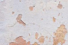 Texturerad knäckt murbruk för bakgrund som vit strilades delvist med en rosa färg, skuggade den spruckna väggen Kan användas som  Arkivbilder
