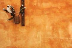 Texturerad orange vägg med blommor arkivfoto