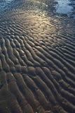 Texturerad sand på en strand Arkivbild