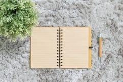 Texturerade den bruna anmärkningsboken för closeupen med den bruna pennan på grå tygcapet bakgrund Arkivfoto