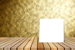 Texturerar den pålagda tabellen för det vita kortet och den suddiga abstrakta guld- väggen bakgrund produktskärmmall 3d business  Arkivbilder