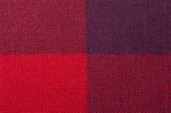 Texturerat tyg med en modell av fyrkanter av skuggor av rött Fotografering för Bildbyråer