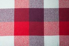Texturerat tyg med en modell av fyrkanter av skuggor av rött, lilor och vit Arkivfoton