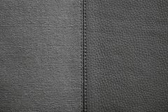 Textures of black color from fabric and leather. The stitched combination of two textures of black color from rough fabric and an imitation leather for abstract Royalty Free Stock Image