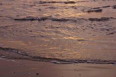 Textures de ressac entrant au coucher du soleil Images stock