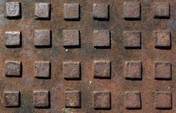 Textures: Manhole Cover Diamon. A square pattern on a rusted manhole cover Stock Image