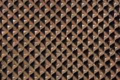 Textures: Manhole Cover Diamon. A square pattern on a rusted manhole cover Stock Photography