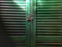 Texturice y encienda y sombree la puerta verde de la ventana Foto de archivo libre de regalías
