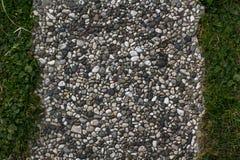 Texturtegelplattor av små stenar och grönt gräs arkivfoton