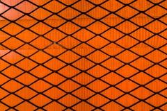 Textuur of achtergrond Een zwart geruit rooster op een oranje heldere achtergrond royalty-vrije stock afbeelding