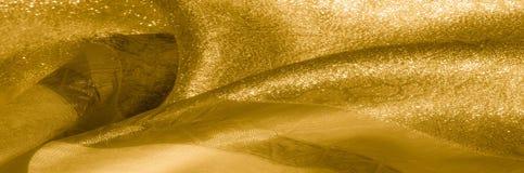 Textuur, achtergrond, patroon Stof - zijdelicht Het goud is yello Royalty-vrije Stock Foto