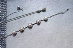 Textuur met pareljuwelen, parels, zilveren kettingen, kristallen van edelstenen, diamanten, diamanten op een lichtgrijze achtergr royalty-vrije stock afbeeldingen