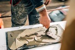 textuur van ceranic de hand die van de arbeider kleefstof op marmer, steen toevoegen royalty-vrije stock afbeelding