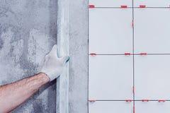 textuur van ceranic De meester legt keramische tegels op de muur en trekt hen uit gebruikend een speciaal niveau stock foto