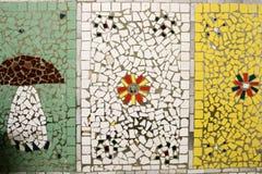 Textuur van een ceramisch mozaïek van glasfragmenten van diverse kleuren met een patroon van bloemen en een paddestoel De achterg stock afbeeldingen