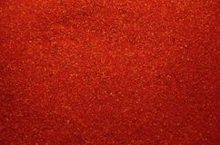 Textuur van een gekleurd korrelig zand dicht omhoog Rode korrels stock foto