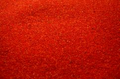 Textuur van een gekleurd korrelig zand dicht omhoog Rode korrels royalty-vrije stock foto