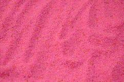 Textuur van een gekleurd korrelig zand dicht omhoog Roze korrels royalty-vrije stock afbeelding