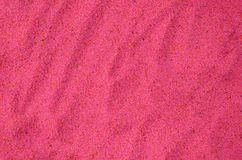 Textuur van een gekleurd korrelig zand dicht omhoog Roze korrels stock fotografie