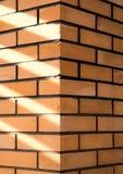 Textuur van een hoek van een bakstenen muur met stralen van zonlicht Stock Foto
