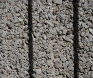 Textuur van een muur van kleine, kleine grijze stenen met twee kuiltjes in het midden stock foto's