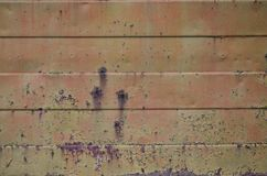 Textuur van een oude oranje metaalmuur met significante schade van blootstelling aan ongunstige weersomstandigheden en dampnes stock fotografie