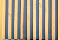 Textuur van gestreepte gele en bruine verticale houten polen en raad met grijze hiaten, spleten De achtergrond royalty-vrije stock foto