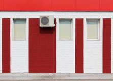textuur van heldere rode bakstenen muur met witte strepen, airconditioner en vensters op een zonnige dag Stock Foto's