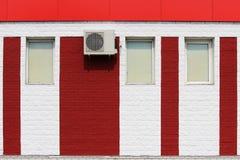 textuur van heldere rode bakstenen muur met witte strepen, airconditioner en vensters op een zonnige dag Stock Fotografie