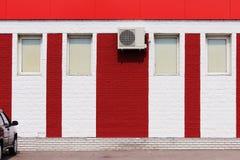 textuur van heldere rode bakstenen muur met witte strepen, airconditioner en vensters op een zonnige dag Stock Afbeelding