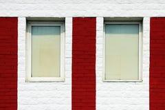 textuur van heldere rode bakstenen muur met witte strepen en vensters op een zonnige dag Stock Afbeelding
