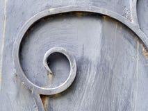 Textuur van ijzer, spiraalvormige krul op oude grijze deur royalty-vrije stock afbeelding