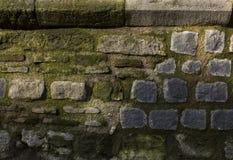 Textuur van kiezelsteen het bedekken Oude bakstenen muur met mos royalty-vrije stock afbeelding