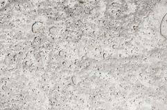 Textuur van kuiltjes gemaakt in grijs beton Stock Foto