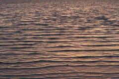 Textuur van ondiepe die golven door purper licht van de het plaatsen zon worden gekleurd Royalty-vrije Stock Afbeelding