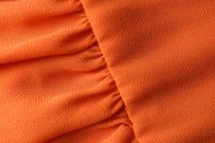 Textuur van oranje stof met vouwen als achtergrond royalty-vrije stock foto