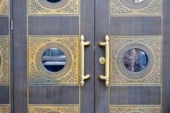 Textuur van oude decoratieve mooie houten deurpoorten met gevormde ornamentenelementen en gouden deurhandvatten De achtergrond royalty-vrije stock foto