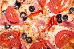 Textuur van smakelijke Italiaanse pizza met ham, tomaten en olijven Stock Fotografie