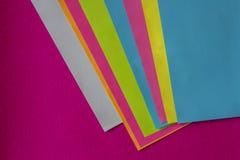 Textuur van weinig bladen van gekleurd document en fuchsiakleurig achtergrond royalty-vrije stock afbeeldingen