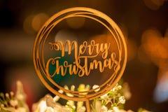 Textzeichen-Deckelstock der frohen Weihnachten auf die Oberseite von Blumensträußen mit Weihnachtsbaum im Hintergrund bokeh Lizenzfreies Stockbild