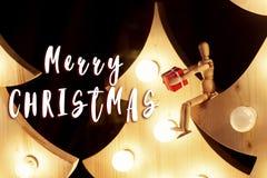 Textzeichen der frohen Weihnachten auf dem hölzernen Spielzeug, das Geschenkboxsitzen gibt Stockfotografie