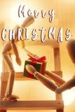 Textzeichen der frohen Weihnachten auf dem hölzernen Spielzeug, das Präsentkarton an c gibt Stockbild
