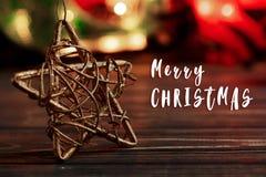 Textzeichen der frohen Weihnachten auf goldenem Stern auf Hintergrund von garlan Lizenzfreies Stockbild