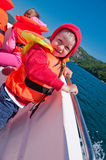 TFloating toddler boy in a boat. The vertical picture of the toddler boy in a lifejacket floating in a boat royalty free stock photo