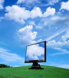 Tft. Monitor on grass with clouds Royalty Free Stock Images