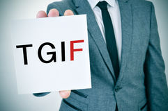 TGIF, Thanks God It is Friday. A young man in suit shows a signboard with the word TGIF, Thanks God It is Friday, written in it Royalty Free Stock Image