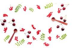Thème de baie Groseille rouge, cerise, cuillères en bois et feuilles sur le copyspace blanc de vue supérieure de fond photo stock