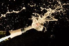 Thème de célébration avec l'explosion d'éclabousser le vin mousseux de champagne sur le fond noir photo libre de droits